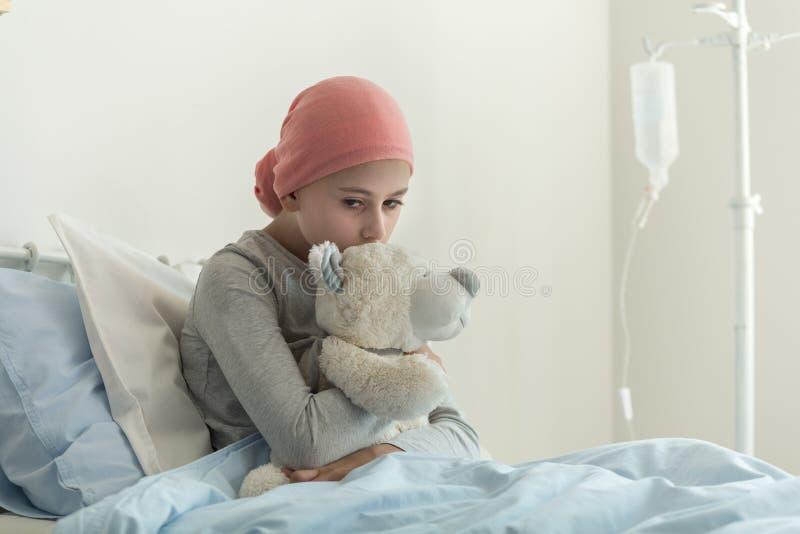 Krankes Mädchen mit dem Kopftuch, das Teddybären nahe bei Tropfenfänger in dem Gesundheitszentrum umarmt lizenzfreies stockfoto