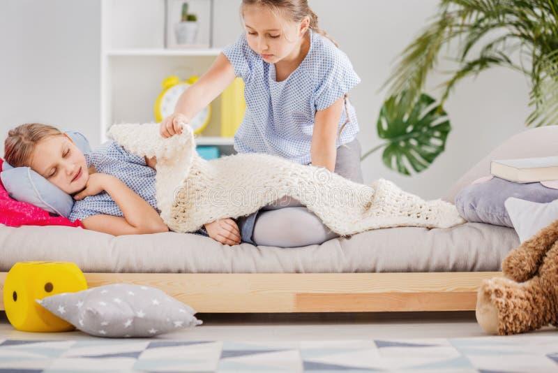 Krankes Mädchen und ihre Schwester lizenzfreie stockbilder