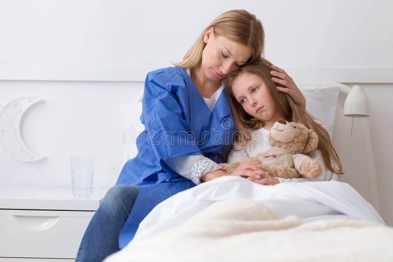 Krankes trauriges Mädchen und ängstlichmutter im Krankenhaus stockfotografie