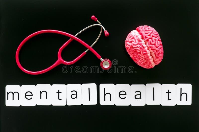 Krankheit des Gehirnkonzeptes mit Kopie, Gehirn und Stethoskop der psychischen Gesundheit auf Draufsicht des schwarzen Hintergrun stockfoto