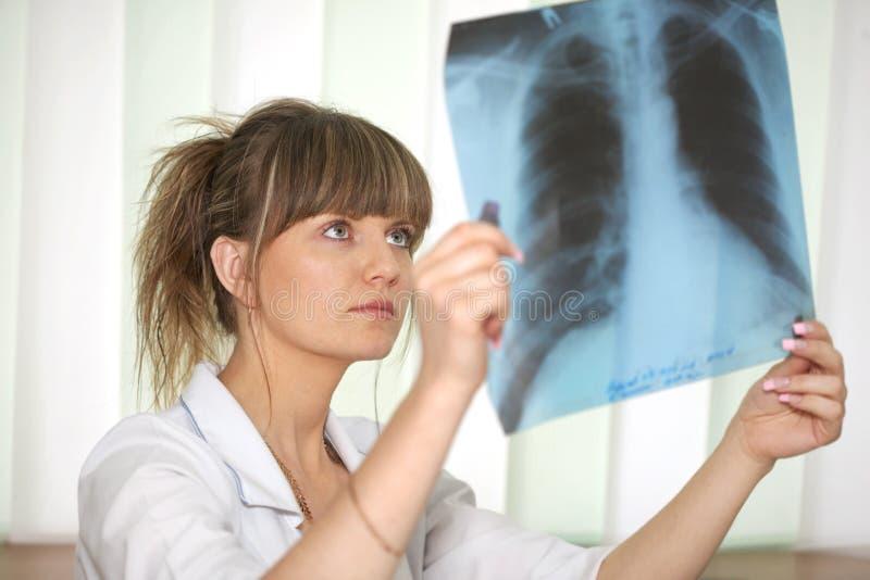 Krankheit. Weiblicher Doktor, der einen Röntgenstrahl überprüft
