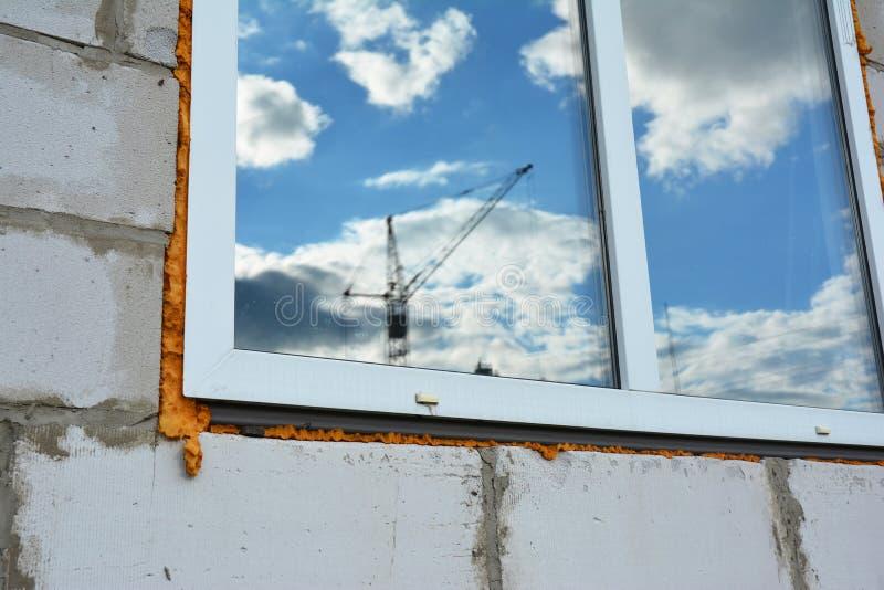 Krankonstruktion i fönsterspegelreflexion på oavslutad byggande huskonstruktion arkivfoton