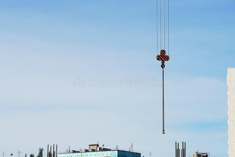 Krankrok med remmar för konstruktionen av en bostads- byggnad Närbild blå himmel, klibba för konstruktionsmonteringar arkivfoto