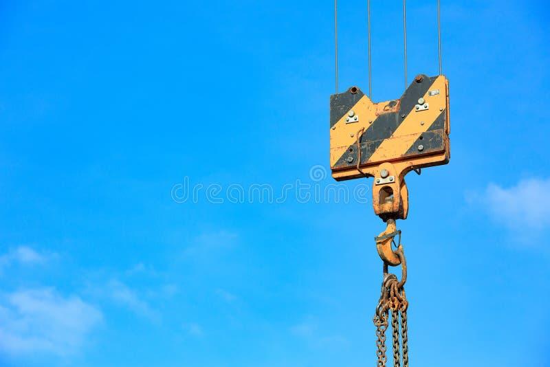 Kranpåfyllningkrok mot himlen med slingor och kedjan fotografering för bildbyråer