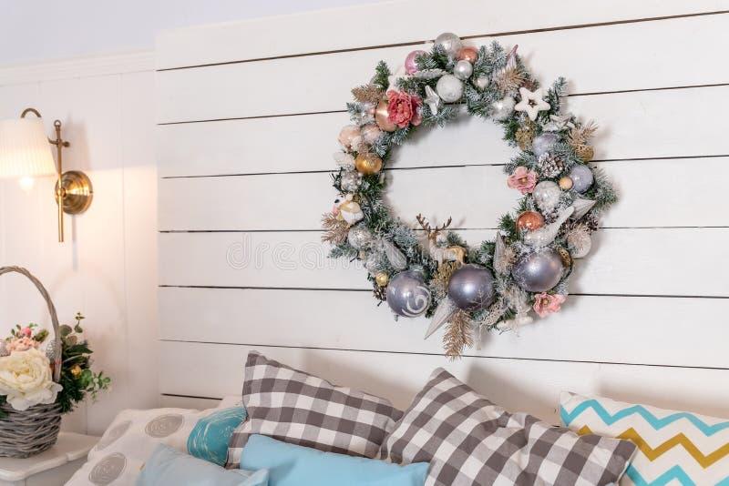 Krans av julbollar ovanför sängen Garnering för nytt år i sovrummet i mjuka rosa och blåa färger Jul fotografering för bildbyråer