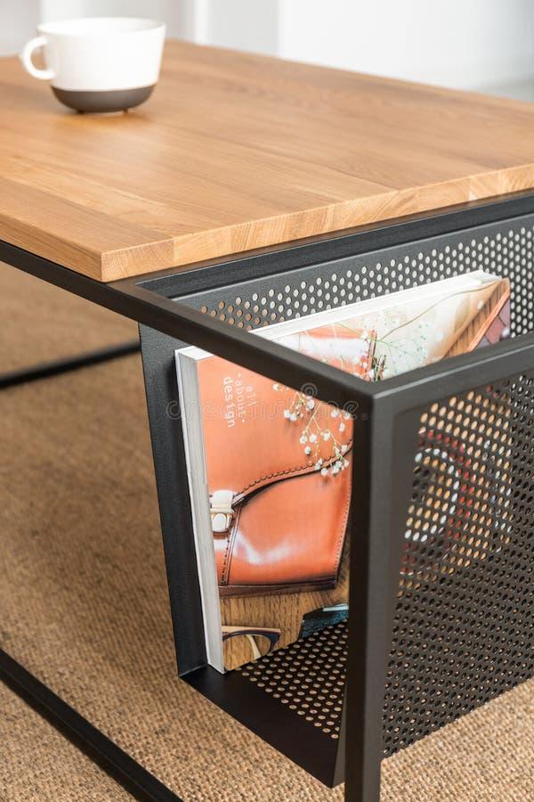 Krant in metaalmand naast houten lijst aangaande tapijt in minimaal woonkamerbinnenland stock afbeeldingen