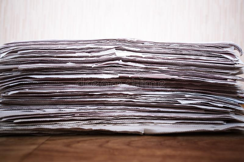 Kranten op de houten lijst worden en worden gestapeld gevouwen die stock afbeelding