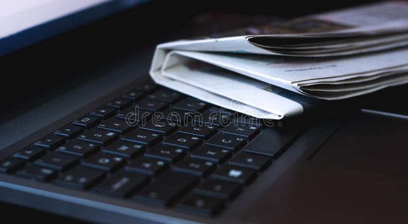 Kranten op laptop Online nieuws stock afbeeldingen