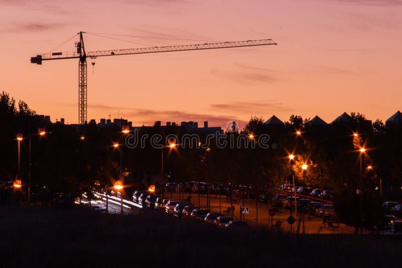 Krantorn på solnedgången i en stad med tända lyktor royaltyfri foto