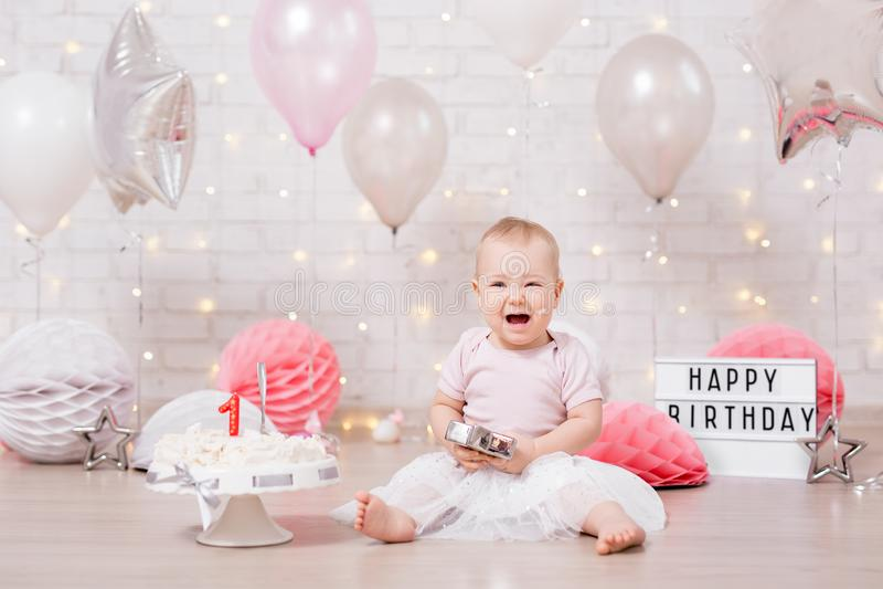 Kraschat skriande partibegrepp - behandla som ett barn flickan och den slog kakan över tegelstenväggen med ljus och ballonger royaltyfria bilder