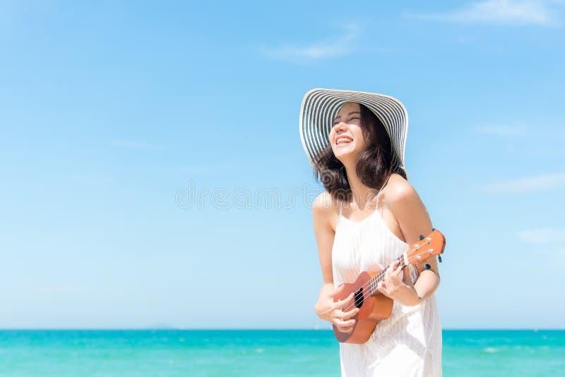 Krasnodar Gegend, Katya Riechende asiatische Frauen, die eine Ukulele auf dem Strand, so glücklich und Luxus im Feiertagssommer s lizenzfreies stockfoto