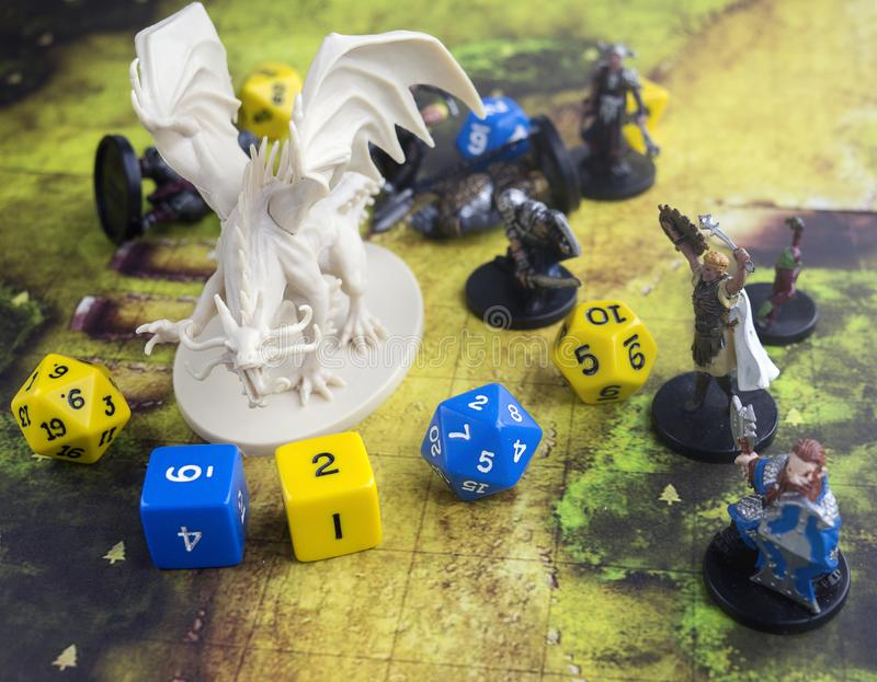 Krasnodar, Russia, 23 May 2019: Playing dungeons and dragons game. Map with a figure of dragon and plastic figures of rpg characte. Rs, dices scattered royalty free stock photography