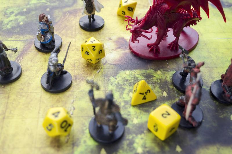 Krasnodar, Russia, 23 May 2019: Playing dungeons and dragons game. Map with a figure of dragon and plastic figures of rpg characte. Rs, dices scattered royalty free stock image