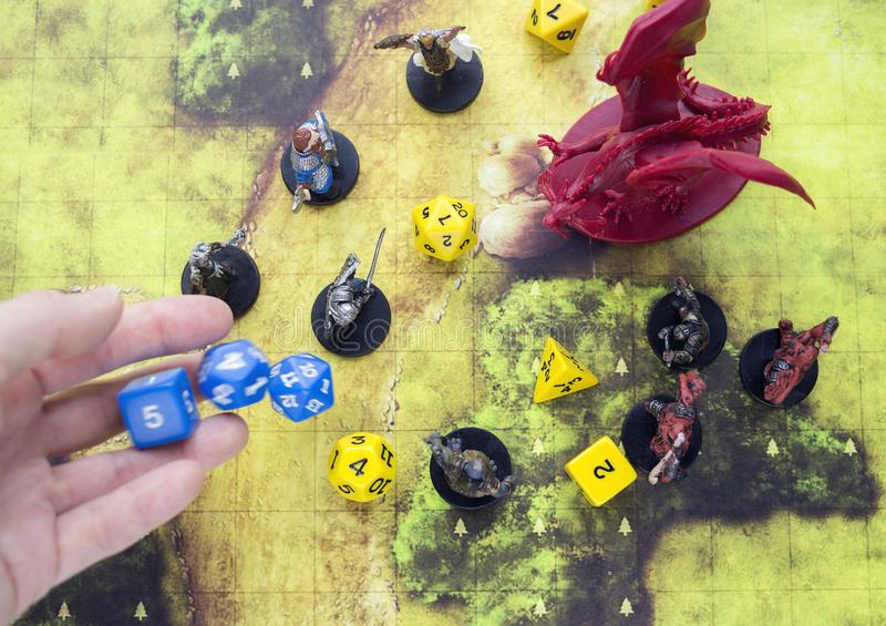 Krasnodar, Russia, 23 May 2019: Playing dungeons and dragons game. Map with a figure of dragon and plastic figures of rpg characte. Rs, dices scattered.  Hand royalty free stock images