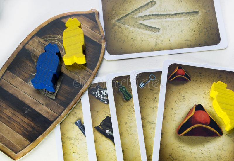 KRASNODAR/RUSSIAN FEDERATION – JUNE 28, 2017: Playing Cartagena board game, cards, wooden figures of pirates, boat. Hobby royalty free stock photo