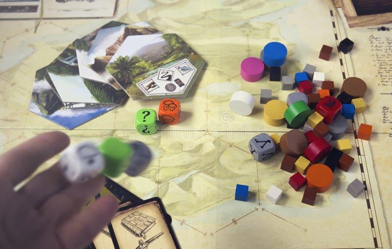 Krasnodar, Russland, am 23. Mai 2019: Spielen von Robinson Crusoe Board Game Karte, deckt mit Ziegeln, w?rfelt und h?lzerne Chips lizenzfreie stockfotografie