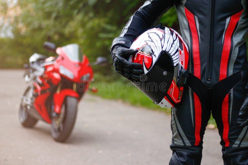 KRASNOJARSK, RUSSIA - 27 agosto 2018: Bello motociclista in ingranaggio pieno che tiene un casco del motociclo Freccia R del casc immagine stock libera da diritti