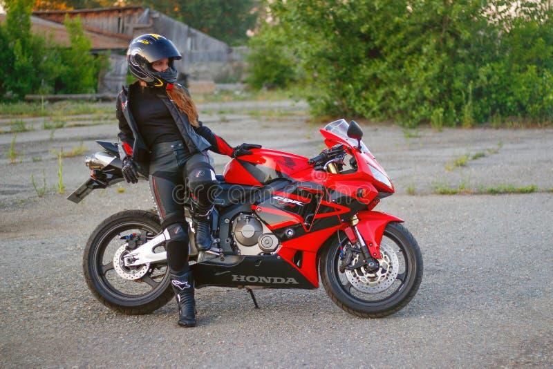 KRASNOJARSK, RUSSIA - 23 giugno 2018: Bello motociclista della ragazza in ingranaggio pieno e casco su Honda rosso e nero 2005 CB fotografie stock libere da diritti