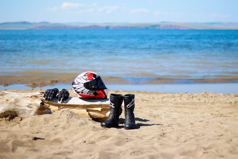 KRASNOYARSK, РОССИЯ - 9-ое августа 2018: Ботинки, перчатки и шлем лежа на пляже Оборудование на пляже морем стоковое изображение rf