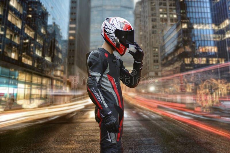 KRASNOYARSK, RÚSSIA - 30 DE MAIO DE 2018: Um motociclista na engrenagem e no capacete completos está no meio da rua Cidade da noi imagens de stock