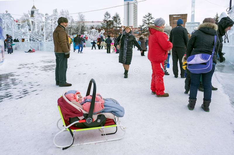 Small child is lying in a wheelchair-sled against the backdrop of a crowd of people in an ice-filled amusement park. stock photos