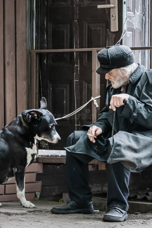 Krasnoyarsk Rosja, 24 Lipiec, 2019: odludny dziad z jego psem siedzi smutnego i dymi papieros Mi?kka ostro??, plama zdjęcia royalty free