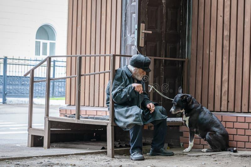 Krasnoyarsk Rosja, 24 Lipiec, 2019: odludny dziad z jego psem siedzi smutnego i dymi papieros Mi?kka ostro??, plama obraz royalty free
