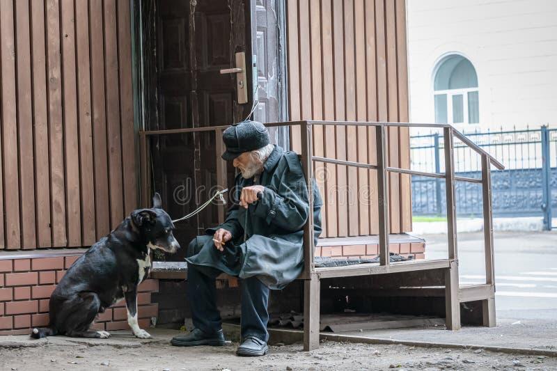 Krasnoyarsk Rosja, 24 Lipiec, 2019: odludny dziad z jego psem siedzi smutnego i dymi papieros Mi?kka ostro??, plama zdjęcia stock