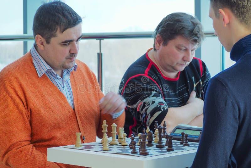 Krasnoyarsk, Rusia 28 de enero de 2018: el torneo de los bombardeos de la ciudad en el club de ajedrez, p?blico se abre Hombres q fotografía de archivo