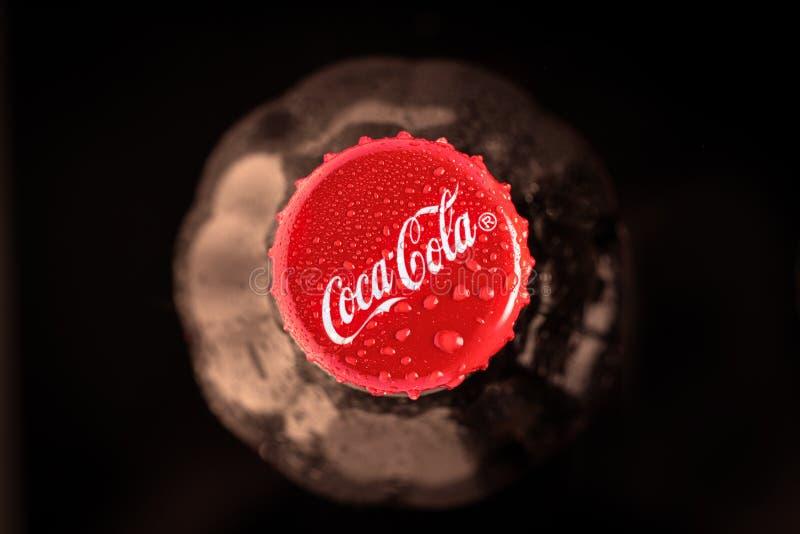 Krasnoyarsk, Rusia 30 de junio de 2019 Botella de la Coca-Cola Visi?n superior Foco oscuro y suave Primer amarillento de las hoja imagenes de archivo