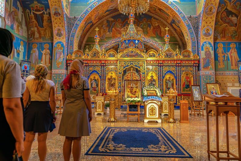 Krasnoyarsk, Rusia, 15 de septiembre de 2019: Mujeres rezan en la Iglesia Ortodoxa, muchos hermosos y viejos íconos imagenes de archivo