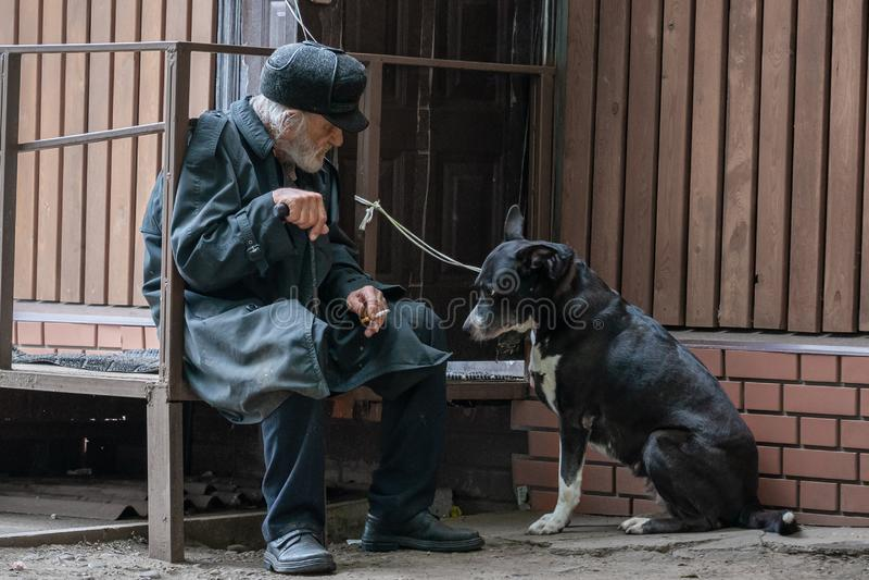 Krasnoyarsk Rusia, el 24 de julio de 2019: un abuelo solitario con su perro sienta triste y fuma el cigarrillo Foco suave, falta  fotografía de archivo