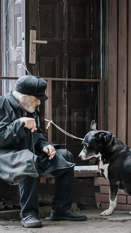 Krasnoyarsk Rusia, el 24 de julio de 2019: un abuelo solitario con su perro sienta triste y fuma el cigarrillo Foco suave, falta  imagen de archivo libre de regalías