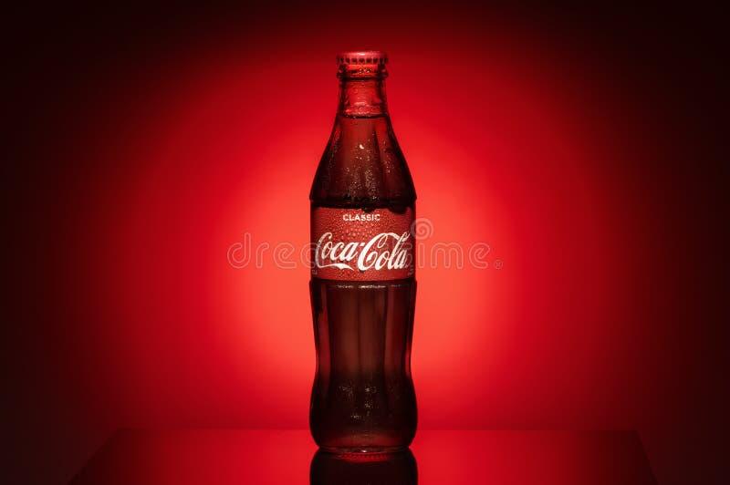 Krasnoyarsk, Rusia, el 29 de junio de 2019: Obra clásica de Coca-Cola en una botella de cristal en rojos de niebla entonados oscu fotos de archivo