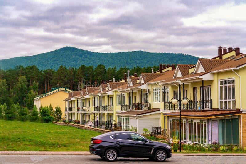 Krasnoyarsk, Rusia, 14 jule 2019: Una fila apenas de nuevas casas urbanas amarillas acabadas Pueblo residencial en el pie de fotografía de archivo
