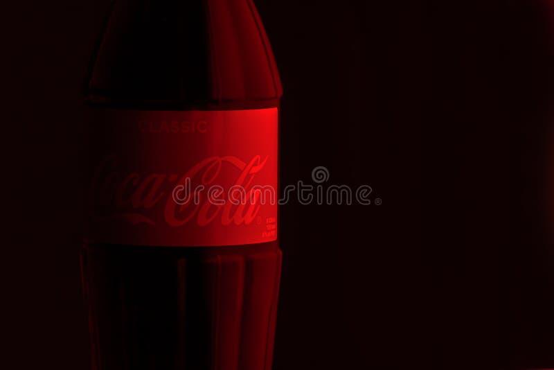 Krasnoyarsk, Rusland, 29 Juni 2019: Coca-Cola-Schrijver uit de klassieke oudheid in een glasfles op rood - zwarte Achtergrond Het stock foto's