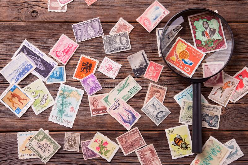 Stamp-collector. Old postage stamps and magnifying glass on a wooden table. Stamp-collector stock photo