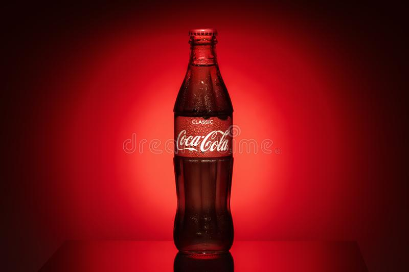 Krasnoyarsk, Russia, 29 June 2019: Coca-Cola Classic in a glass bottle on dark toned foggy reds -black Background. Coke stock photos