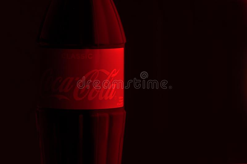 Krasnoyarsk, Russia, 29 June 2019: Coca-Cola Classic in a glass bottle on reds -black Background. Red label Cola logo stock photos