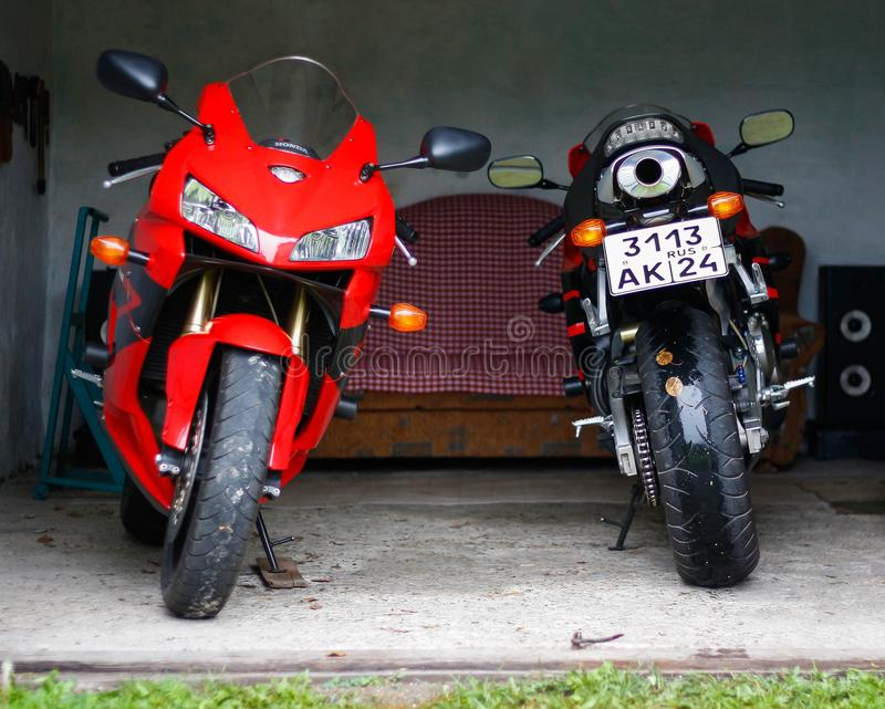 KRASNOYARSK, RUSSIA - September 3, 2018: Two sportbikes in the garage. Red and black sportbike Honda CBR 600 RR 2005 PC37.  royalty free stock photography