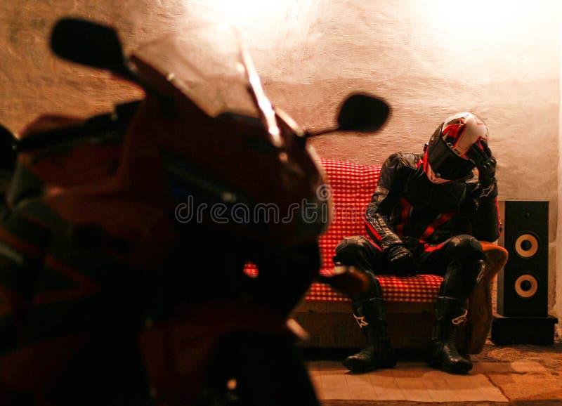 KRASNOYARSK RYSSLAND - Augusti 16, 2018: Motorcyklisten i kugghjulet och hjälmen sitter i garaget och ser motorcykeln royaltyfria bilder