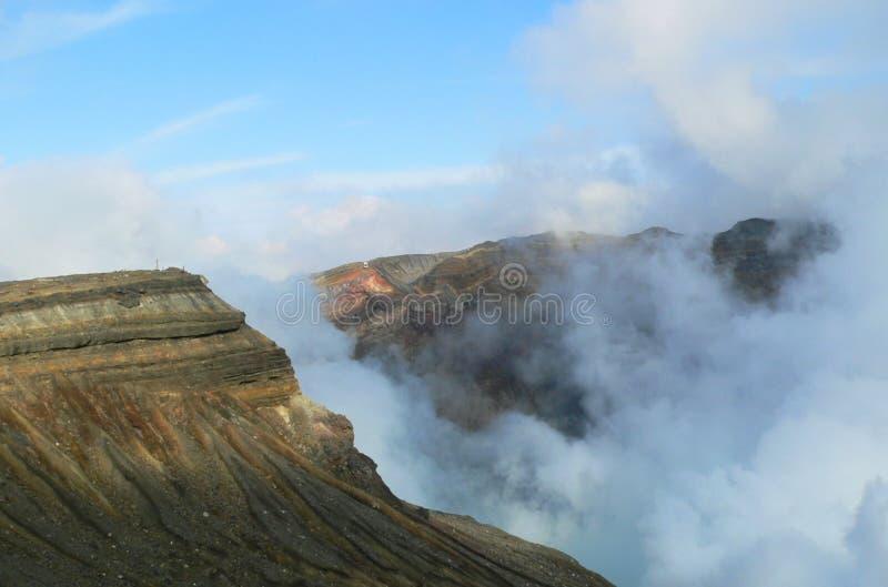 Krater van een vulkaan met vulkanische dampen stock afbeeldingen