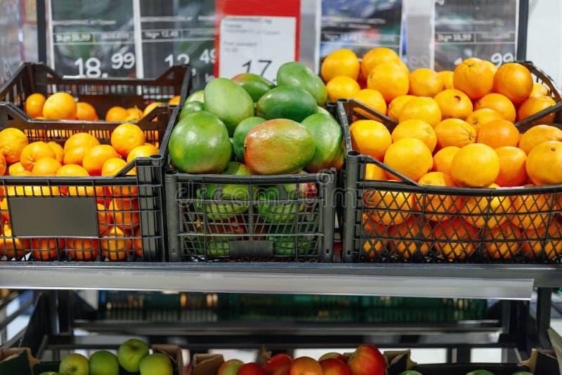 Kratten met rijpe sinaasappel en grapefruits op planken royalty-vrije stock foto's