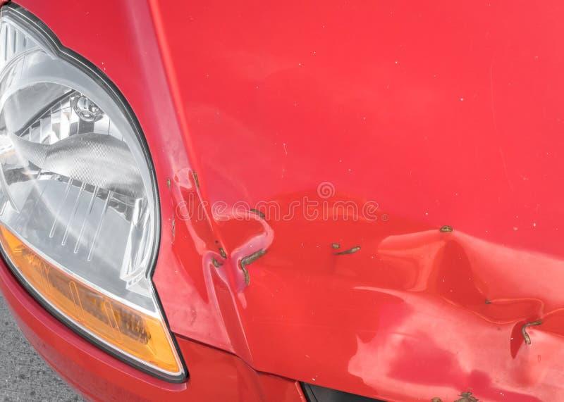 Kratzer und rostige Einbuchtung auf Front des roten Autos lizenzfreie stockfotografie