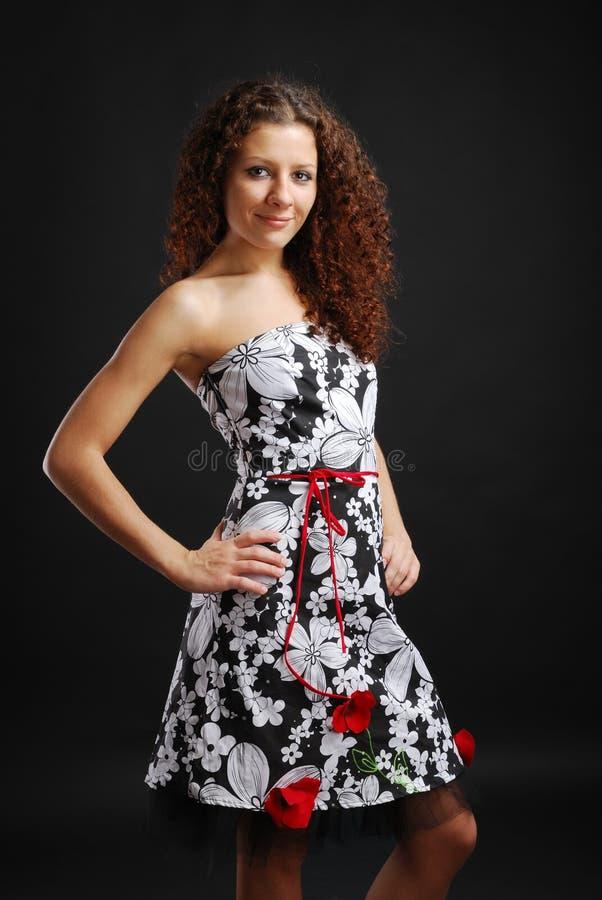Krauses Mädchen in einem Cocktailkleid lizenzfreies stockbild