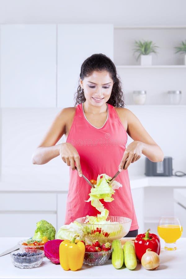 Kraushaarfrau, die zu Hause Salat macht stockbilder