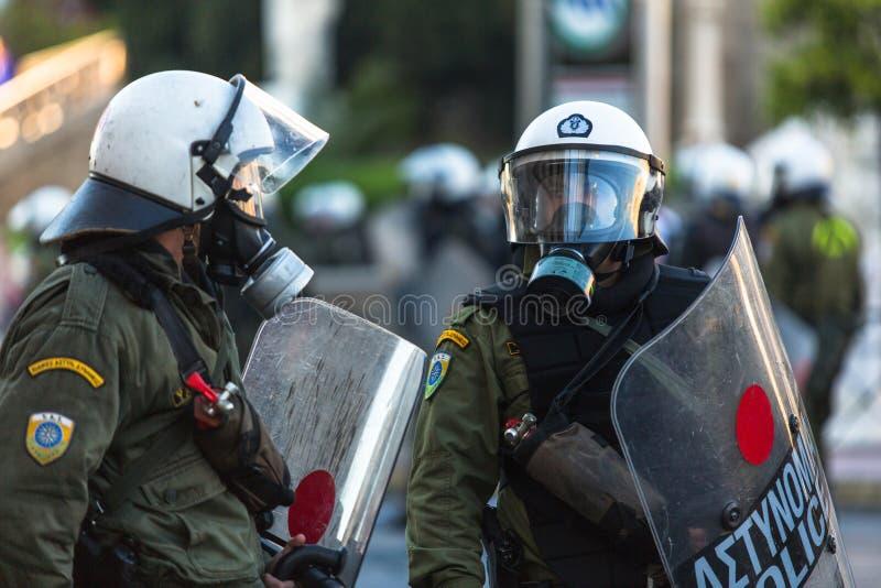 Kravallpolis med deras sköld, taganderäkning under en samla framme av Atenuniversitetet arkivbilder