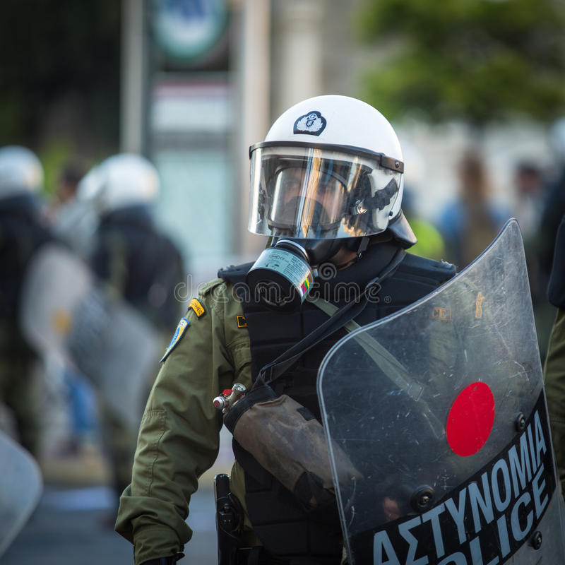 Kravallpolis med deras sköld, taganderäkning under en samla framme av Atenuniversitetet royaltyfria bilder