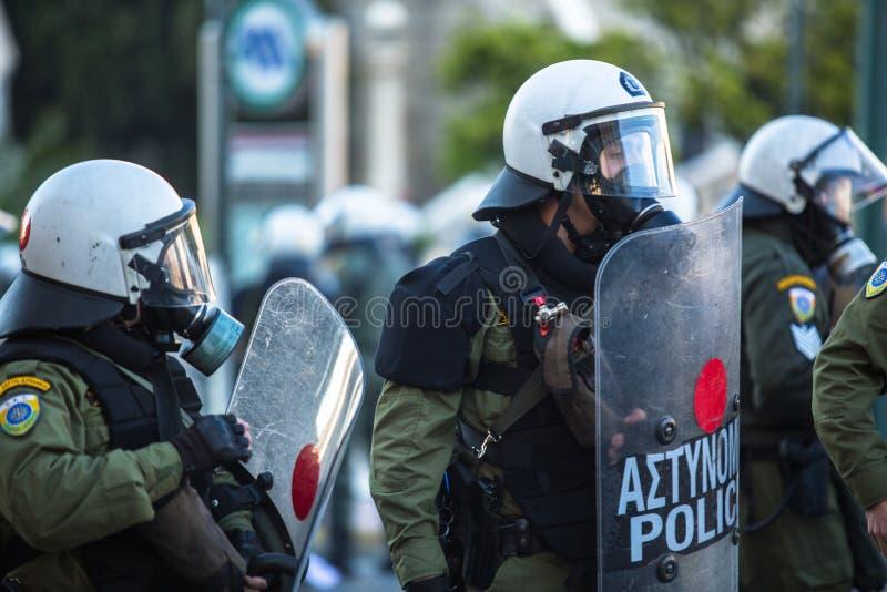 Kravallpolis under en samla framme av Atenuniversitetet, som är under ockupation av personer som protesterar vänstersympatisör oc arkivbild