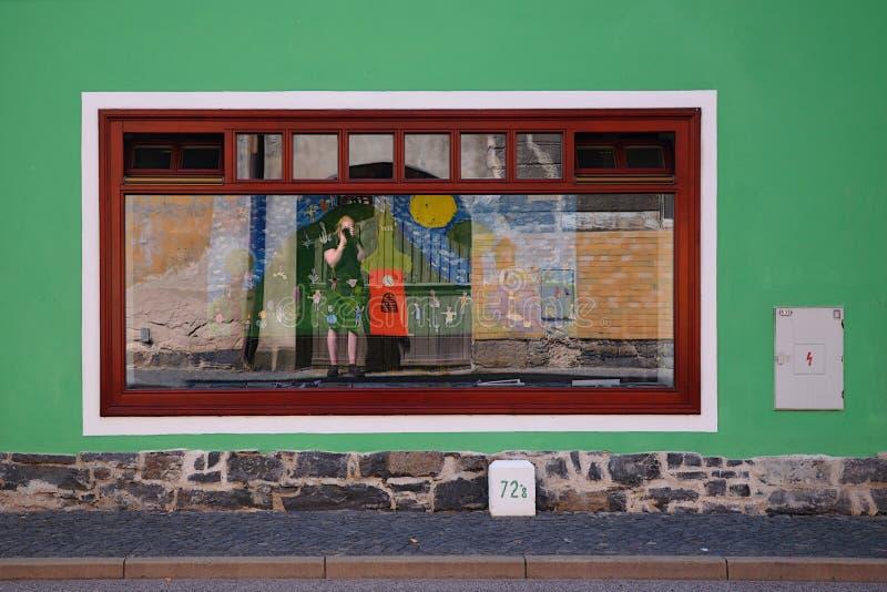 Kravare Machuv kraj, Tjeckien - Juli 14, 2018: barnbilder och den Jiri Igaz fotografen som reflexion shoppar in fönstret av arkivbilder